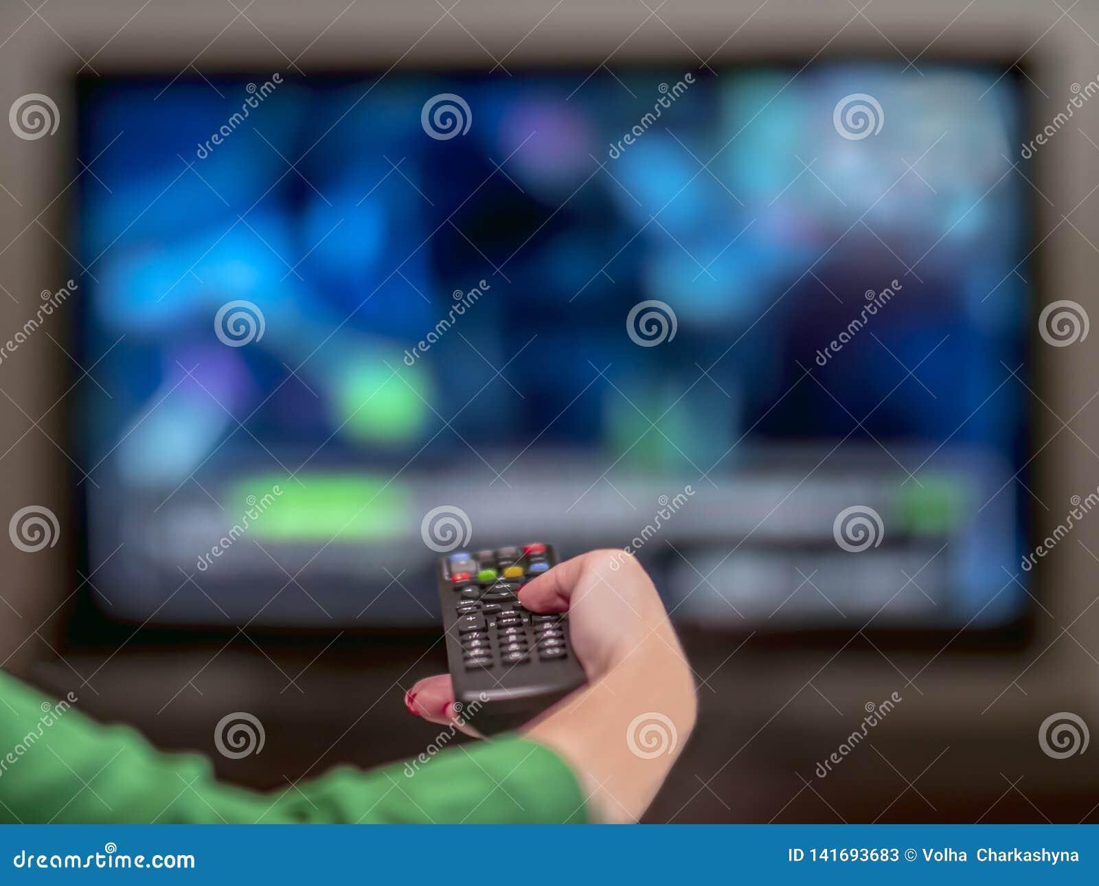 TV à distance dans la main d une femme avec une manucure rouge