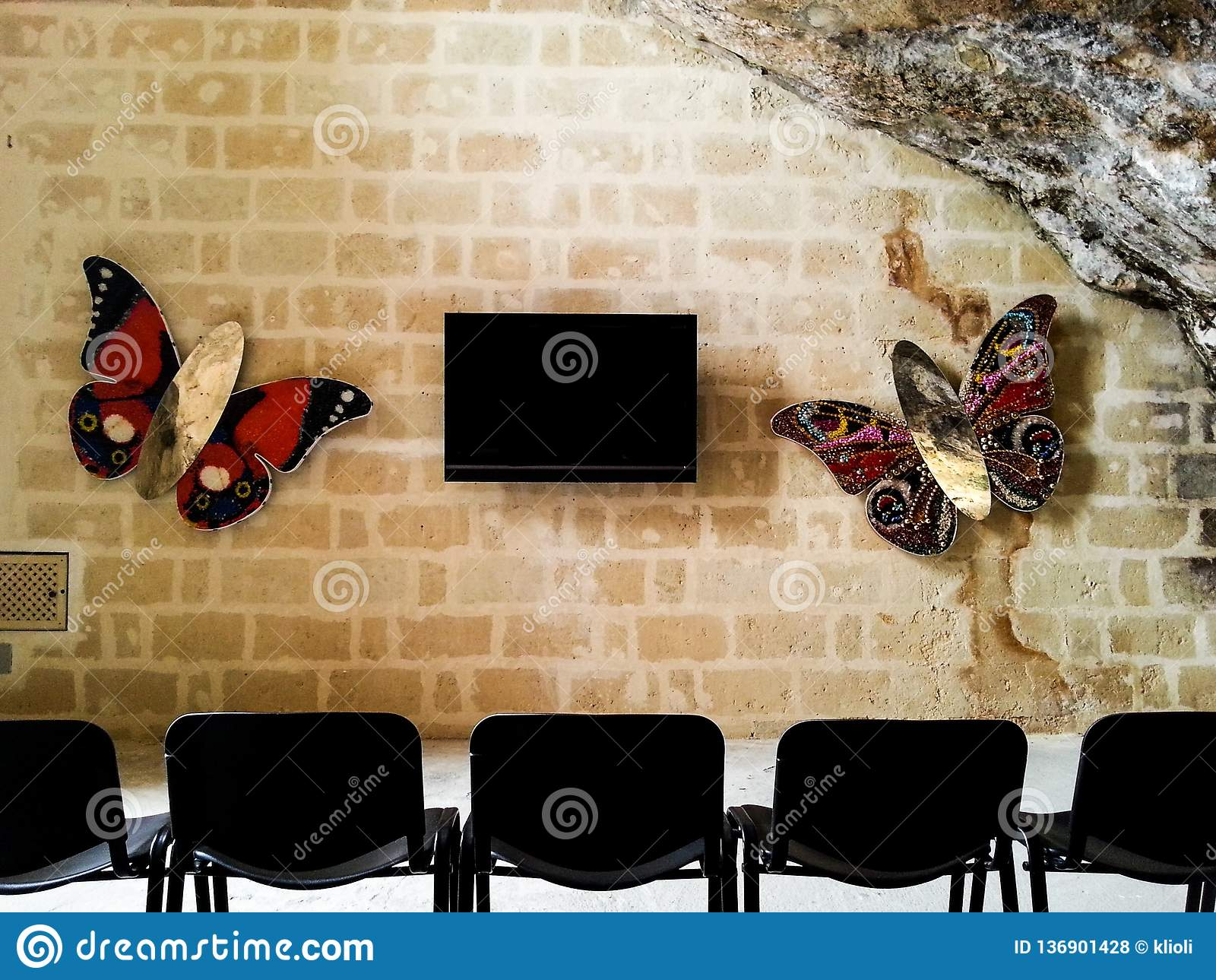 TV hanging on a brick wall surrounded by butterflies in an ancient cave