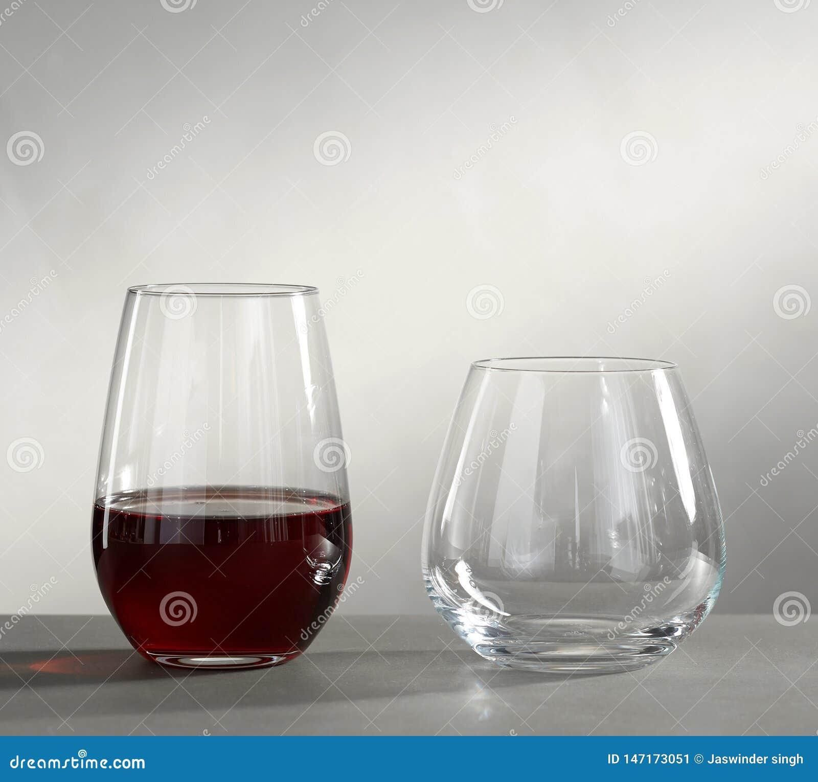 Tv? konjakexponeringsglas som ?r tomma och med alkohol som isoleras p? gr? bakgrund