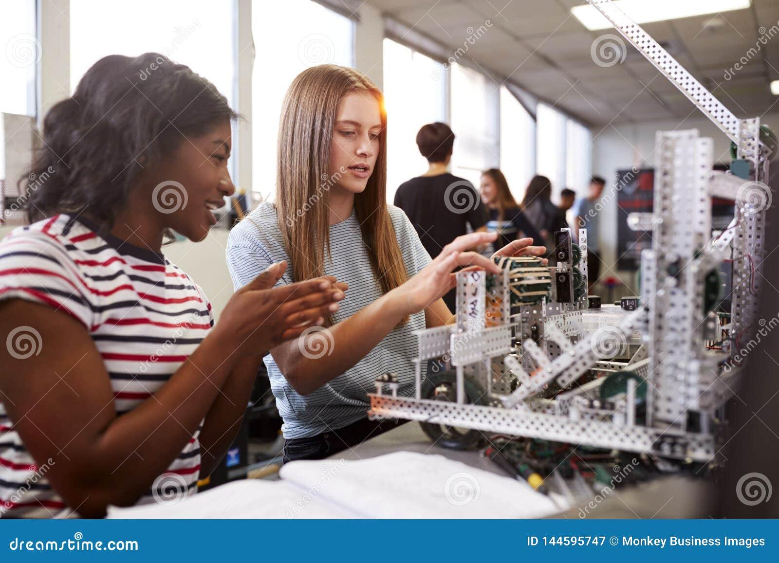 Tv? kvinnliga h?gskolestudenter som bygger maskinen i vetenskapsrobotteknik eller iscens?tter grupp