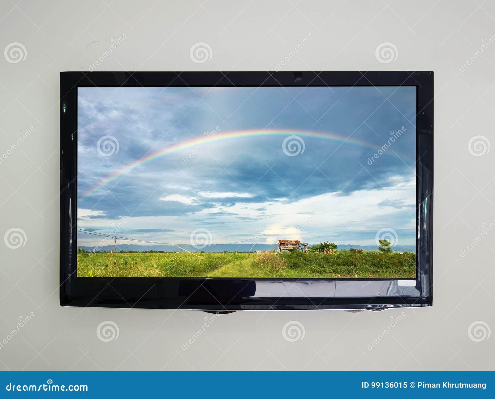 TV llevada en el fondo de la pared con el arco iris en el cielo