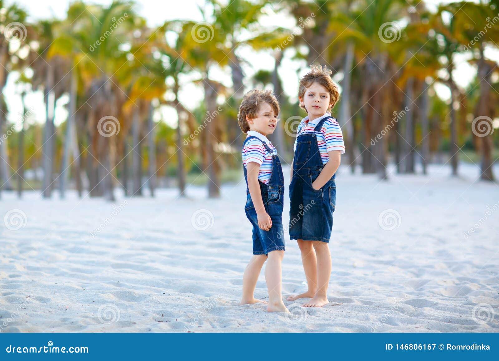 Tv? pojkar f?r sm? ungar som har gyckel p? den tropiska stranden, lyckliga b?sta v?n som spelar, kamratskapbegrepp Syskonbr?der