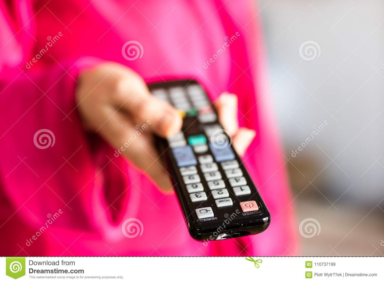 TV remote control held in women& x27;s hands. Switching channels on t