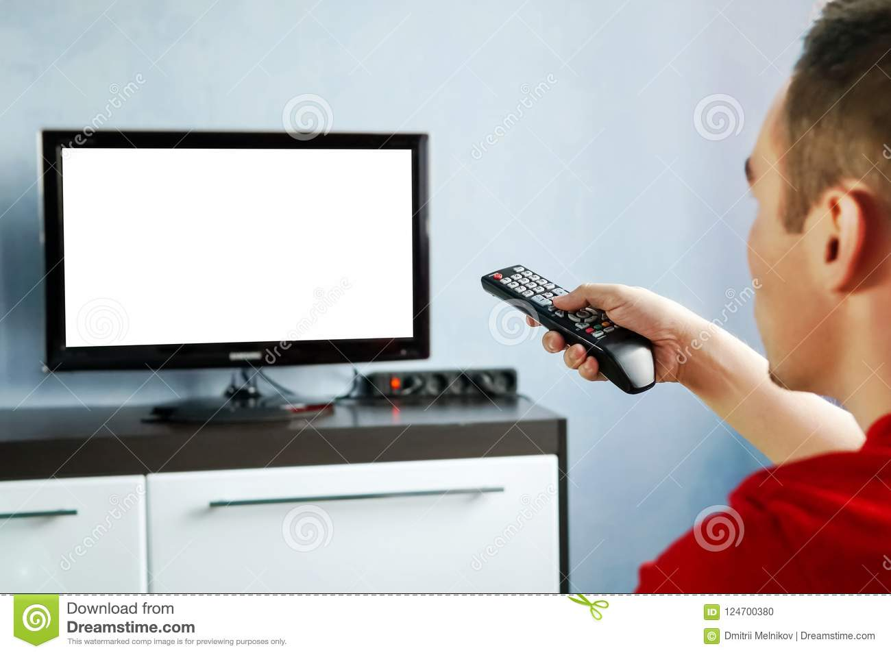 TV Remote Control In Male Hand In Front Of Widescreen TV Set With