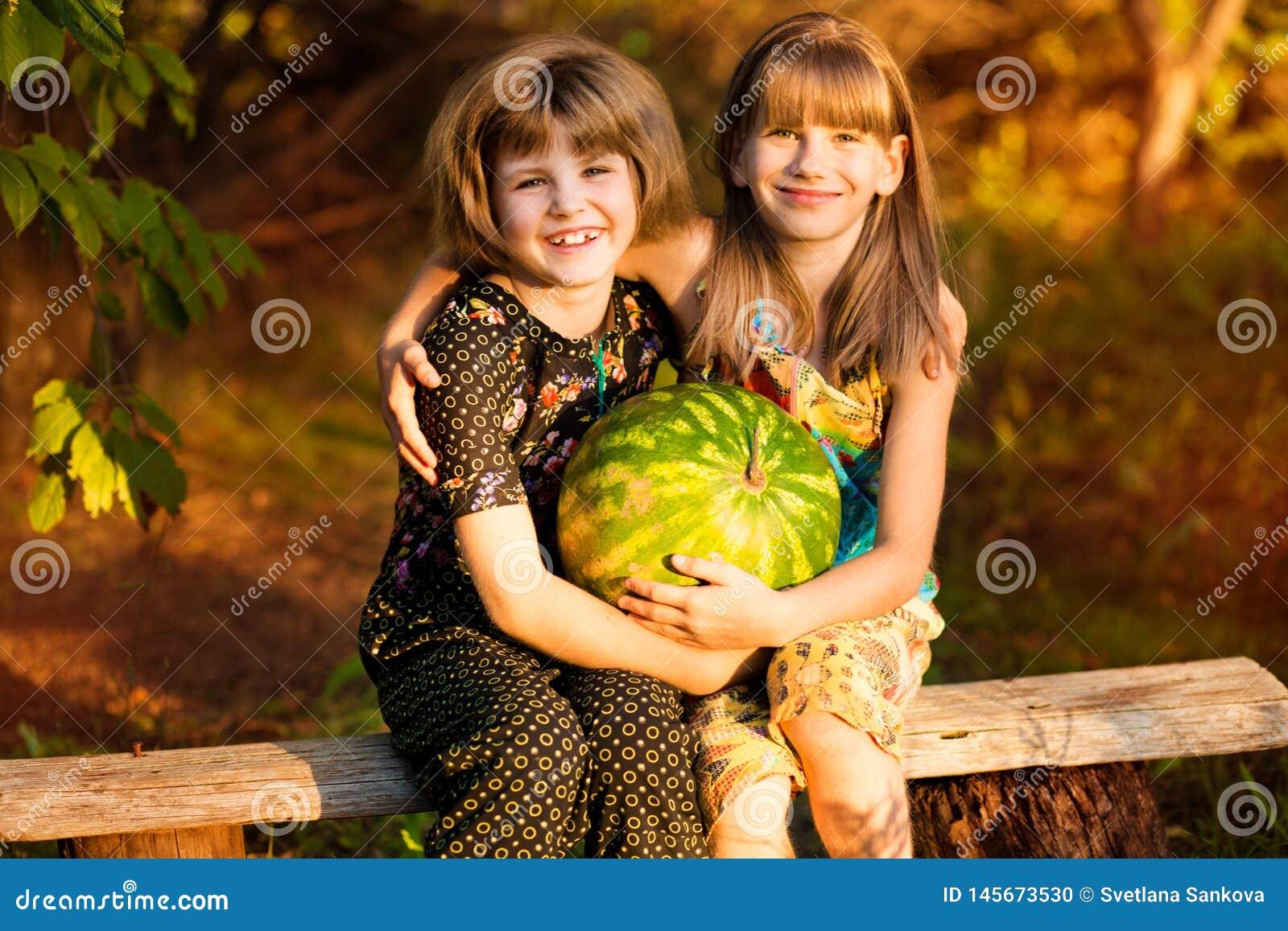 Tv? roliga lilla systrar som utomhus ?ter vattenmelon p? varm och solig sommardag Sund mat f?r ungar