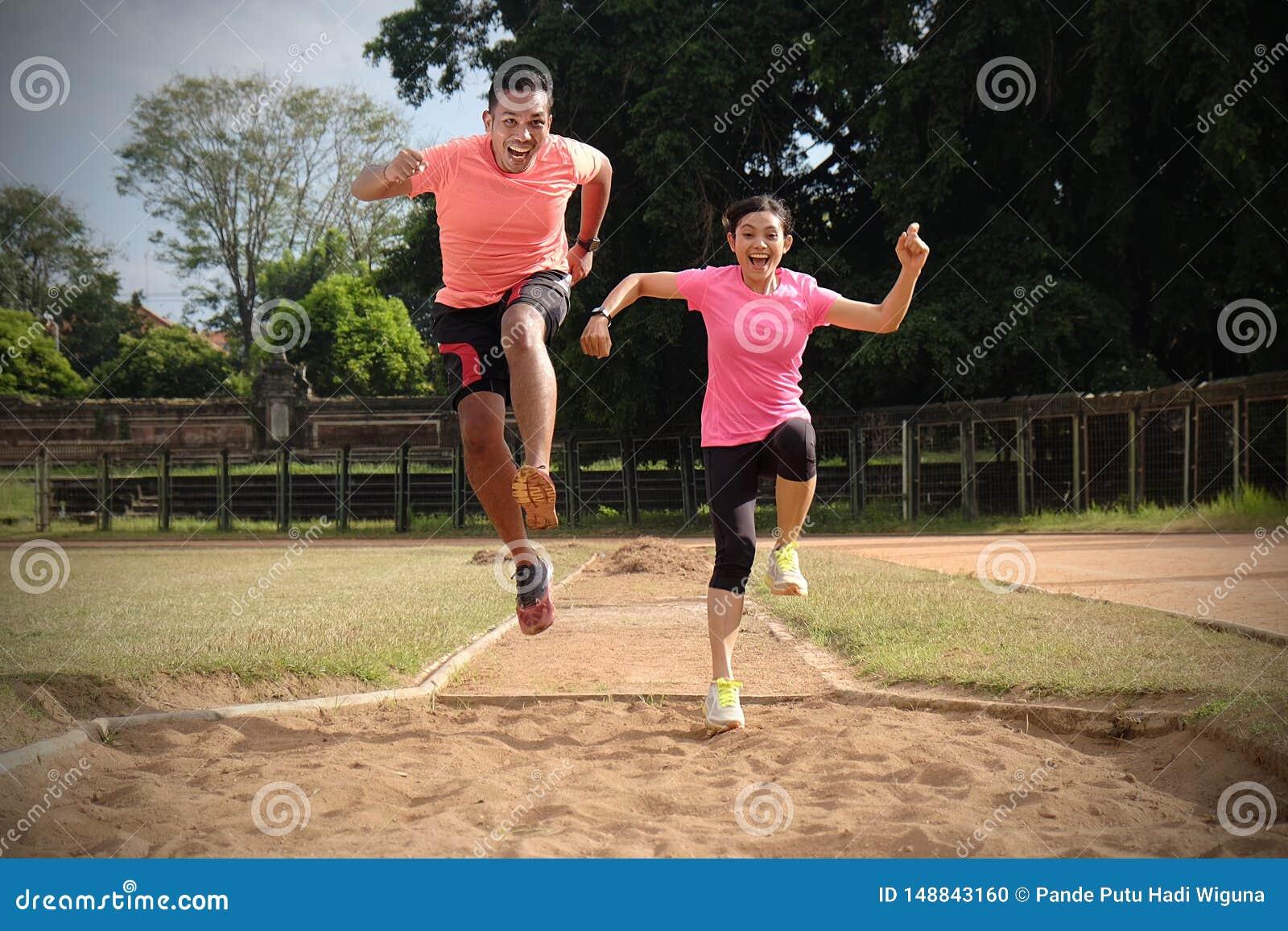 Tv? sportpartners joggar tillsammans p? en solig dag som b?r orange och rosa skjortor De ser de, och leendet, tycker om