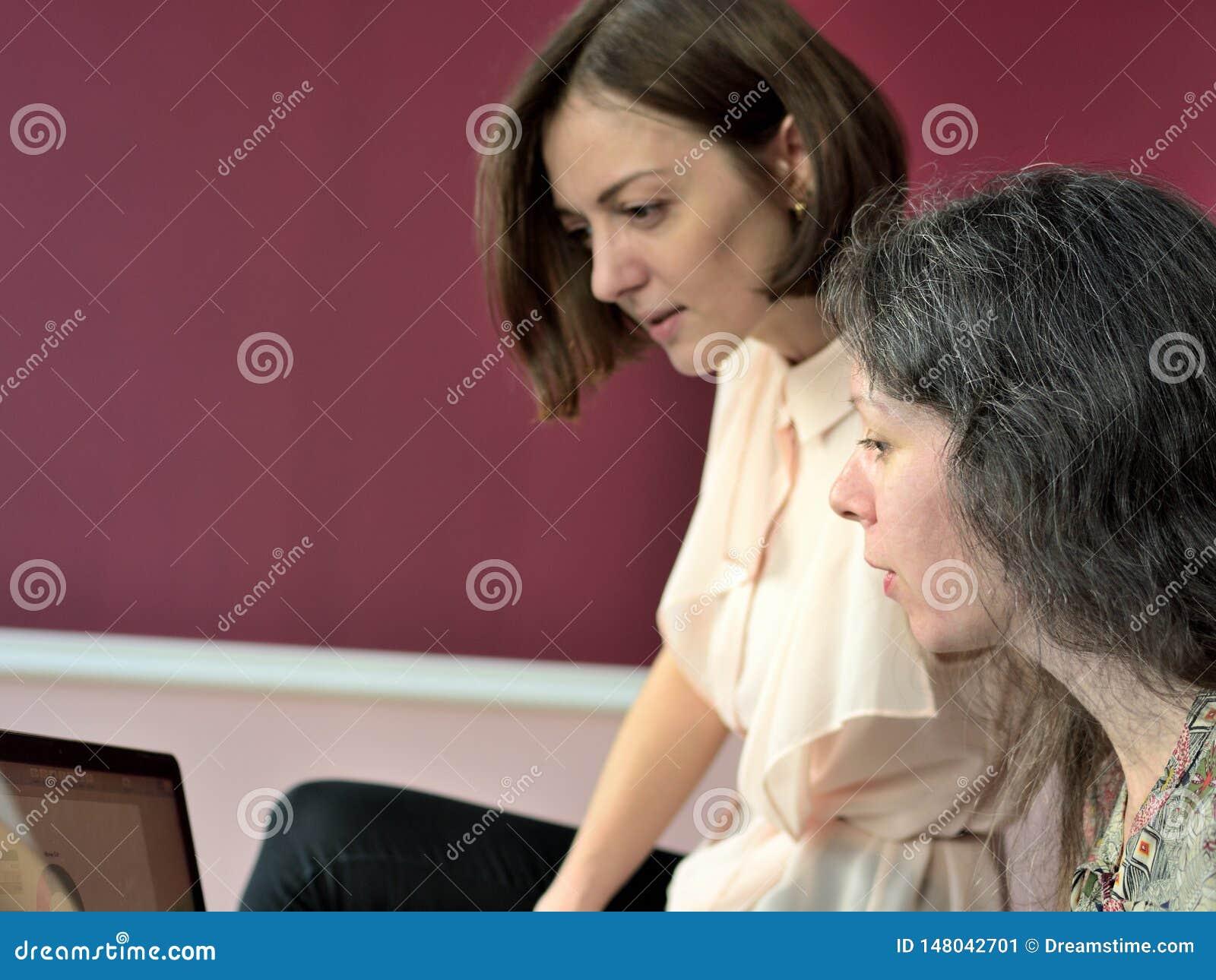 Tv? tillf?lligt kl?dda modeller f?r unga damer sitter p? ett skrivbord i ett tappningkontor och diskuterar modellfrig?rardokument