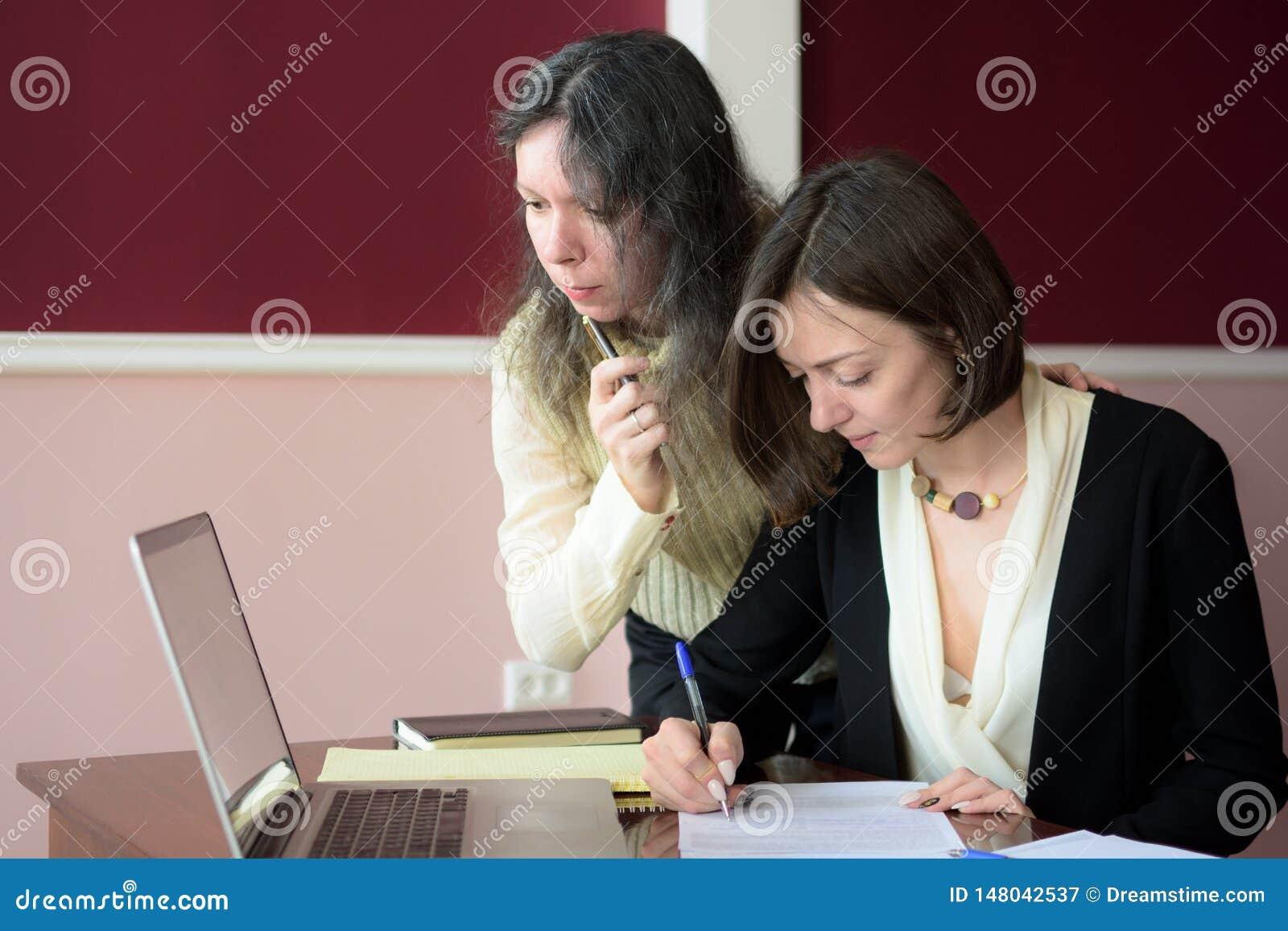 Tv? unga smartly kl?dda kvinnor som ut framme fyller former p? ett tappningkontorsskrivbord av en b?rbar dator