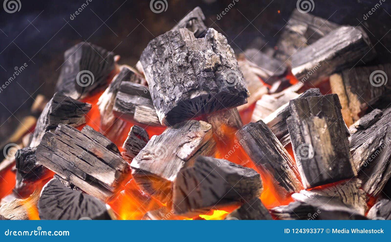 TView dos carvões amassados flamejantes quentes do carvão vegetal que incandescem no poço da grade do BBQ Carvões ardentes para c