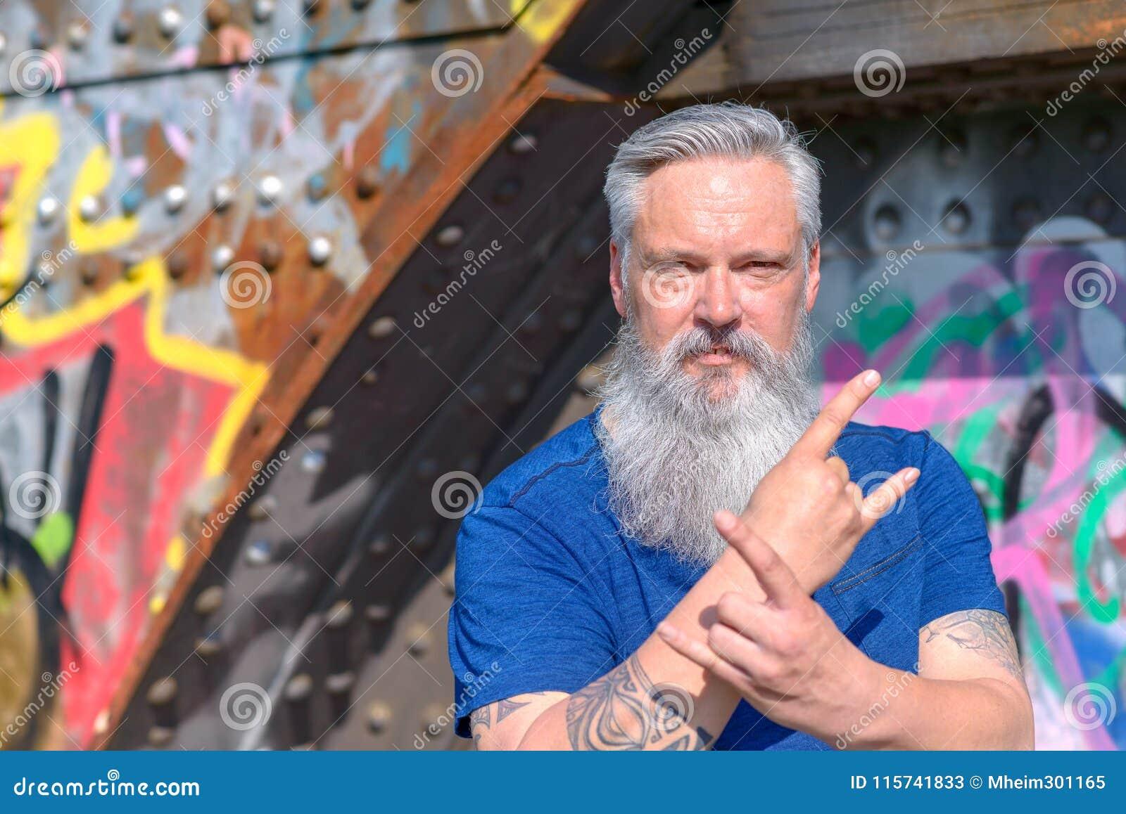 Twardy dojrzały mężczyzna daje diabłów uzbrajać w rogi ręka gest