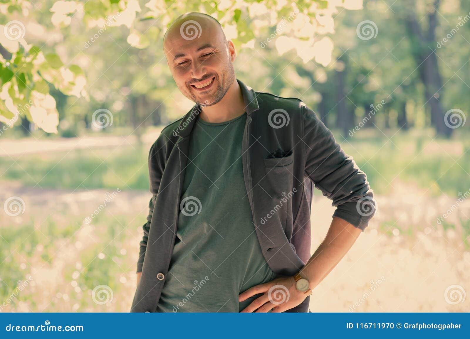 Twarz brodaty uśmiechnięty łysy mężczyzna w parku
