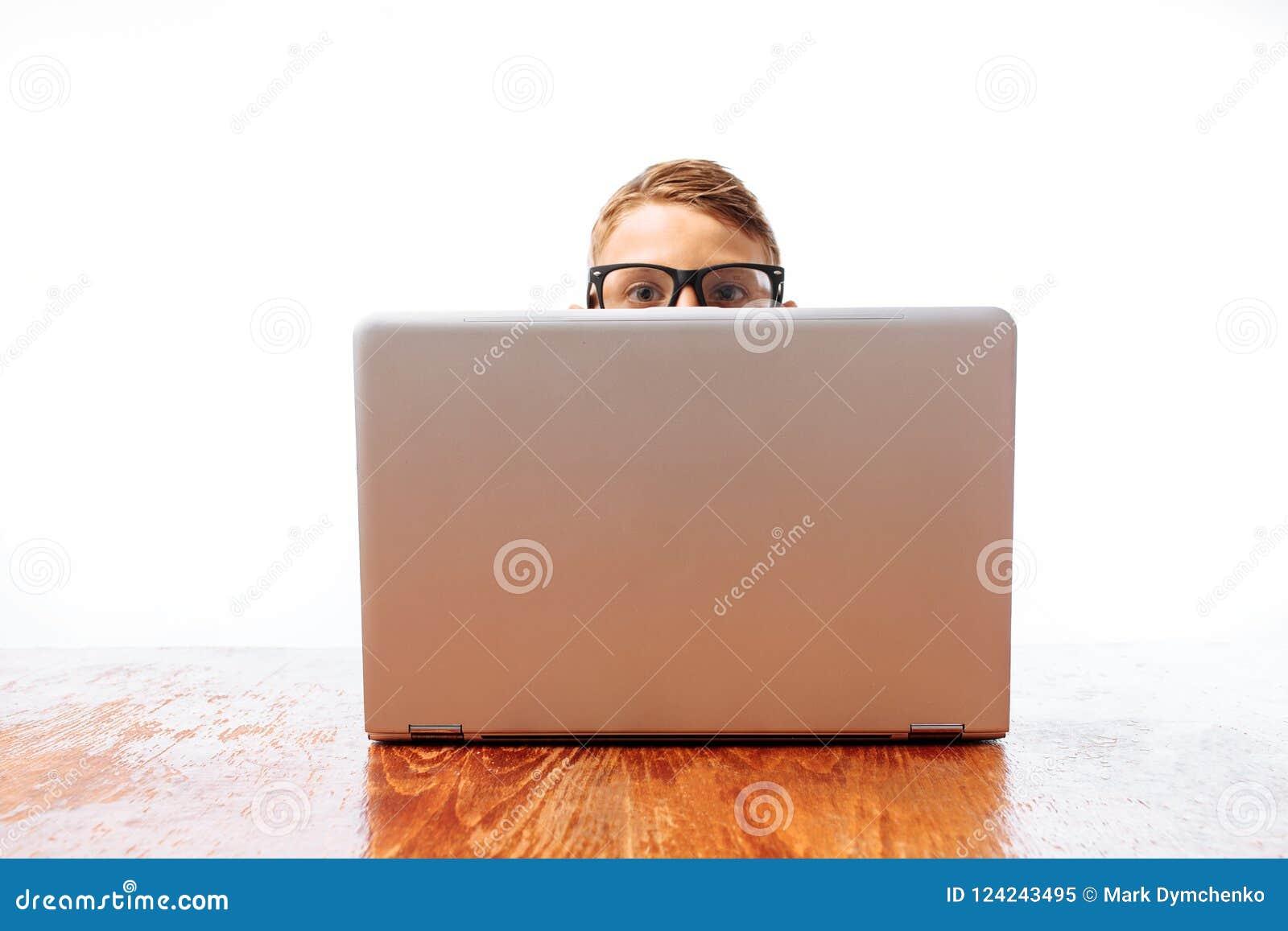 Twarz młody człowiek patrzeje out spod laptopu, nastolatek chuje za laptopem w studiu na białym tle