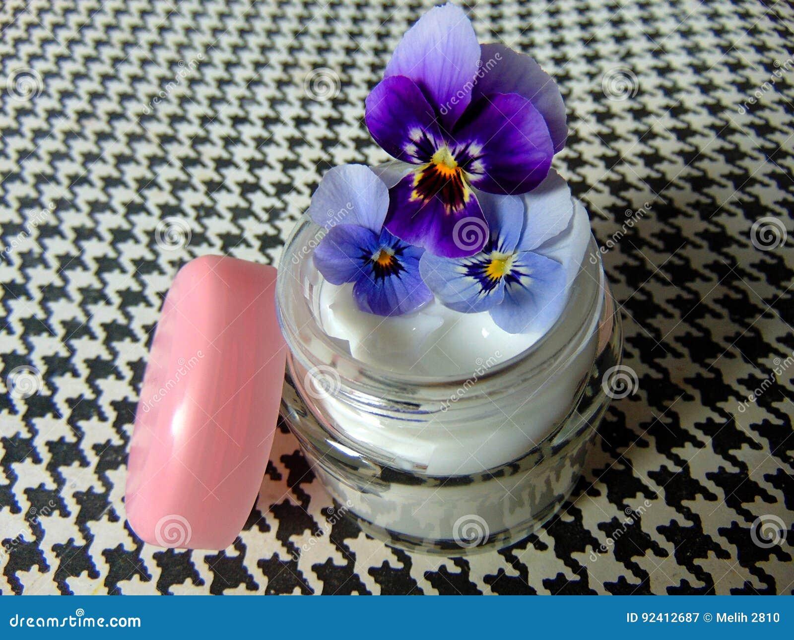Twarzowa śmietanki skóry opieka z purpurowymi kwiatami na dobre