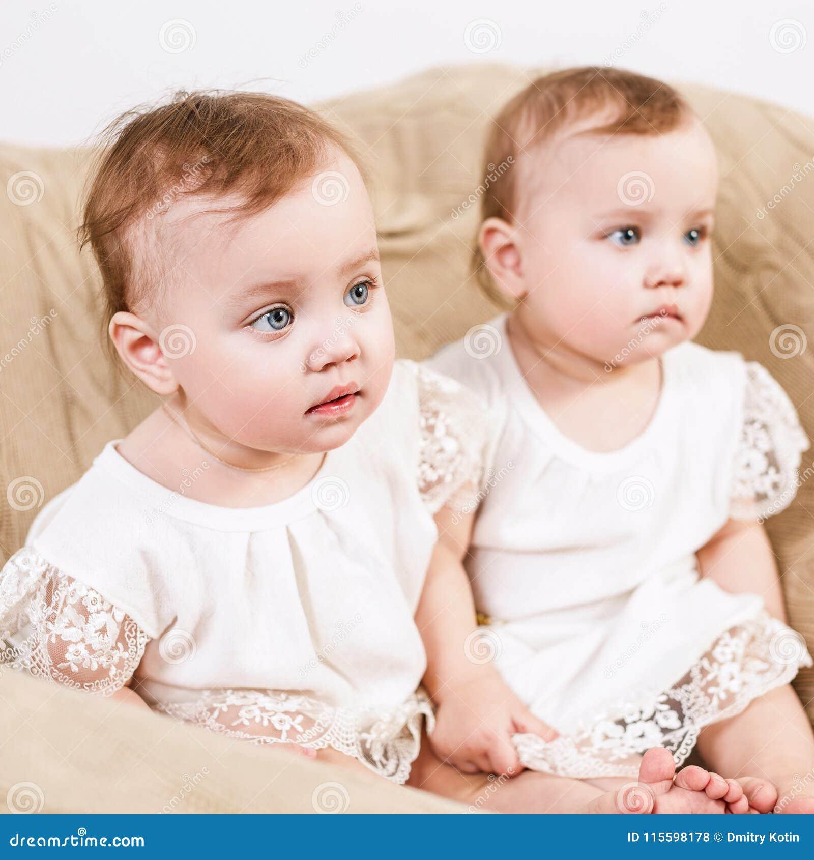 Baby Zitten Stoel.Twee Aanbiddelijke Babytweelingen Die Als Voorzitter Zitten Stock