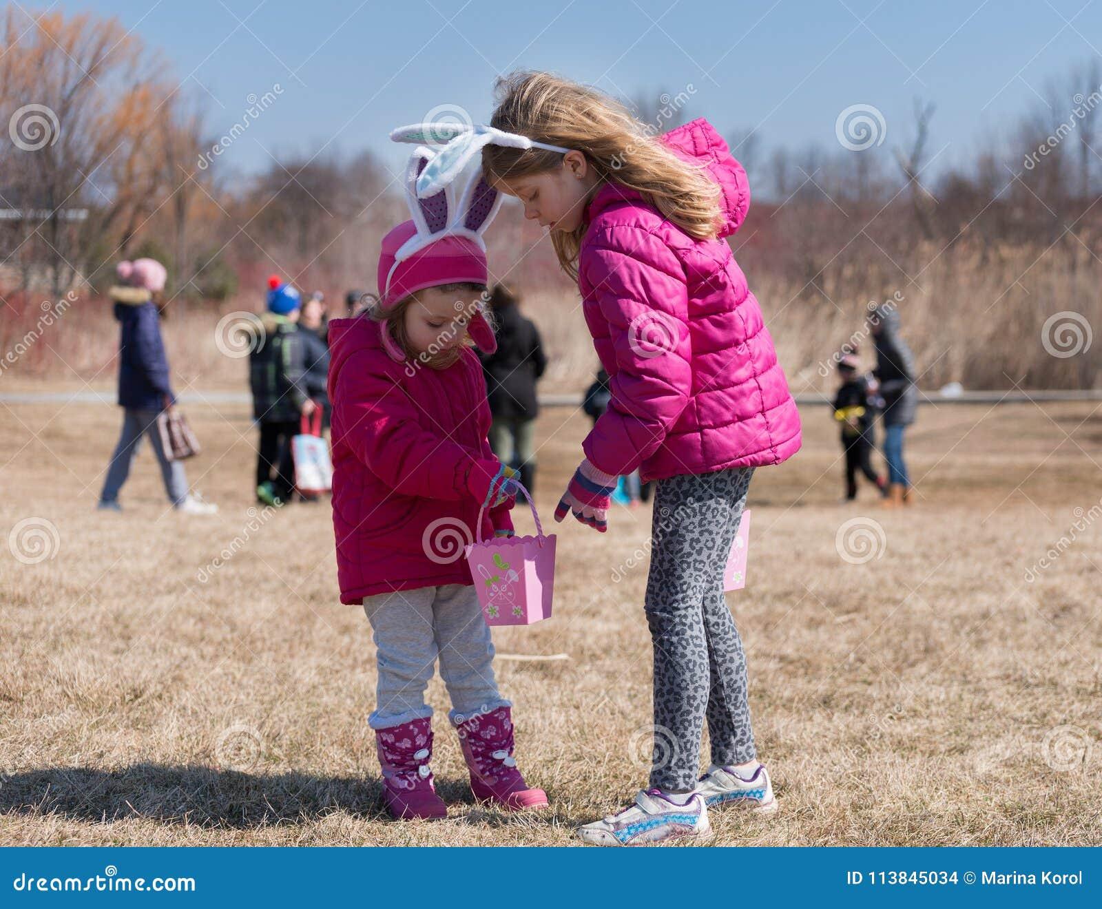 Twee aanbiddelijke blonde Kaukasische zusters die met konijntjes` s oren zijn dragen op de weide deelnemen aan Paasei de Jacht