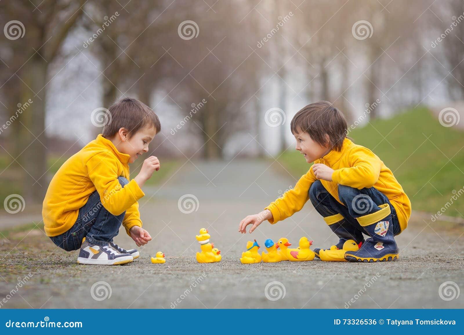 Twee aanbiddelijke kinderen, jongensbroers, die in park met rubber spelen