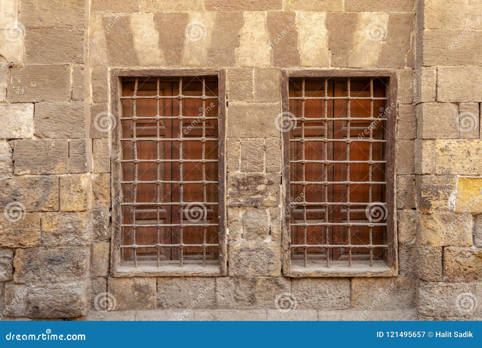 Twee aangrenzende houten vensters met ijzernet over verfraaide steenbakstenen muur, Middeleeuws Kaïro, Egypte