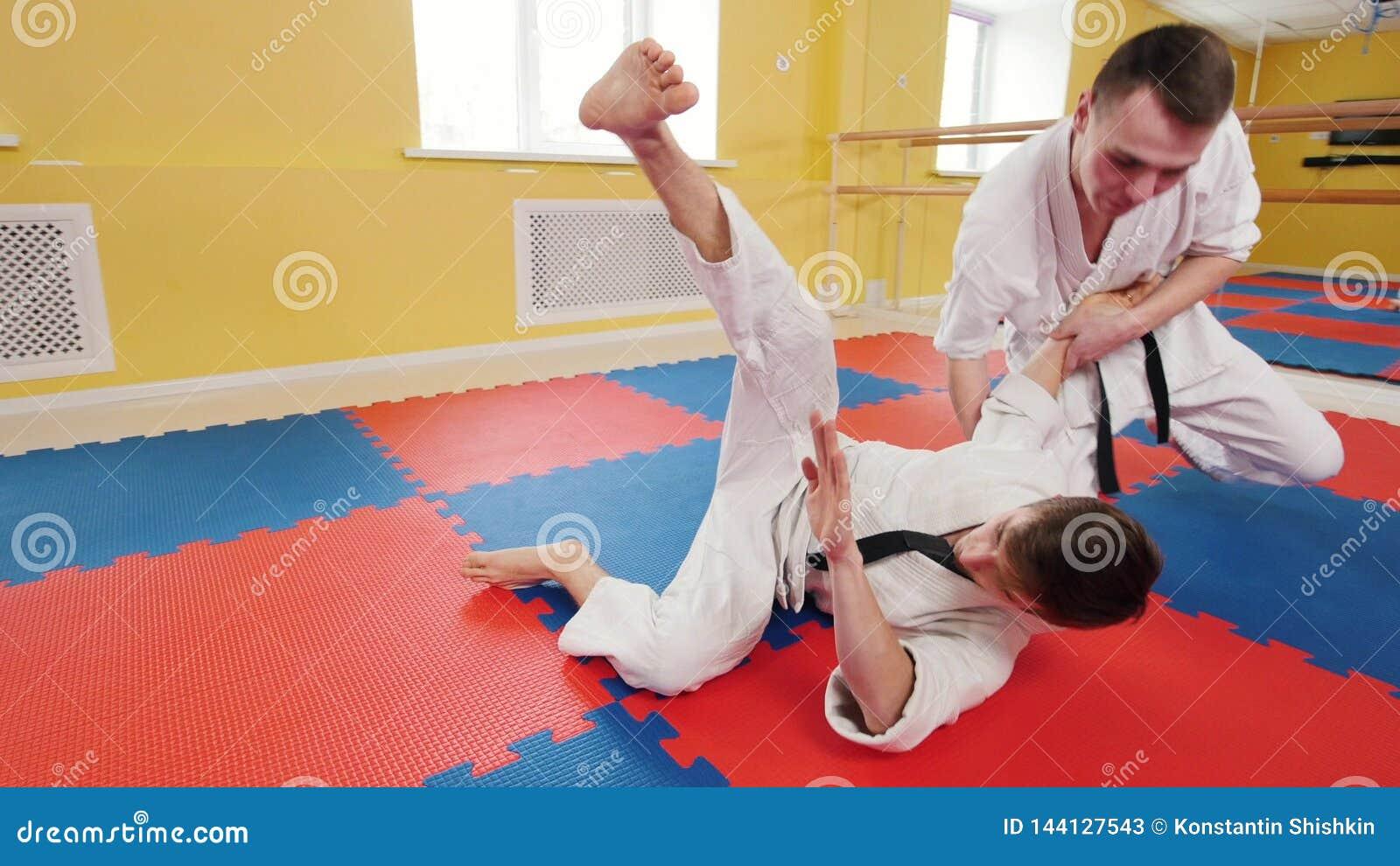 Twee atletische mensen die hun aikidovaardigheden in de studio opleiden Een mens grijpt zijn tegenstander en werpt hem op de vloe