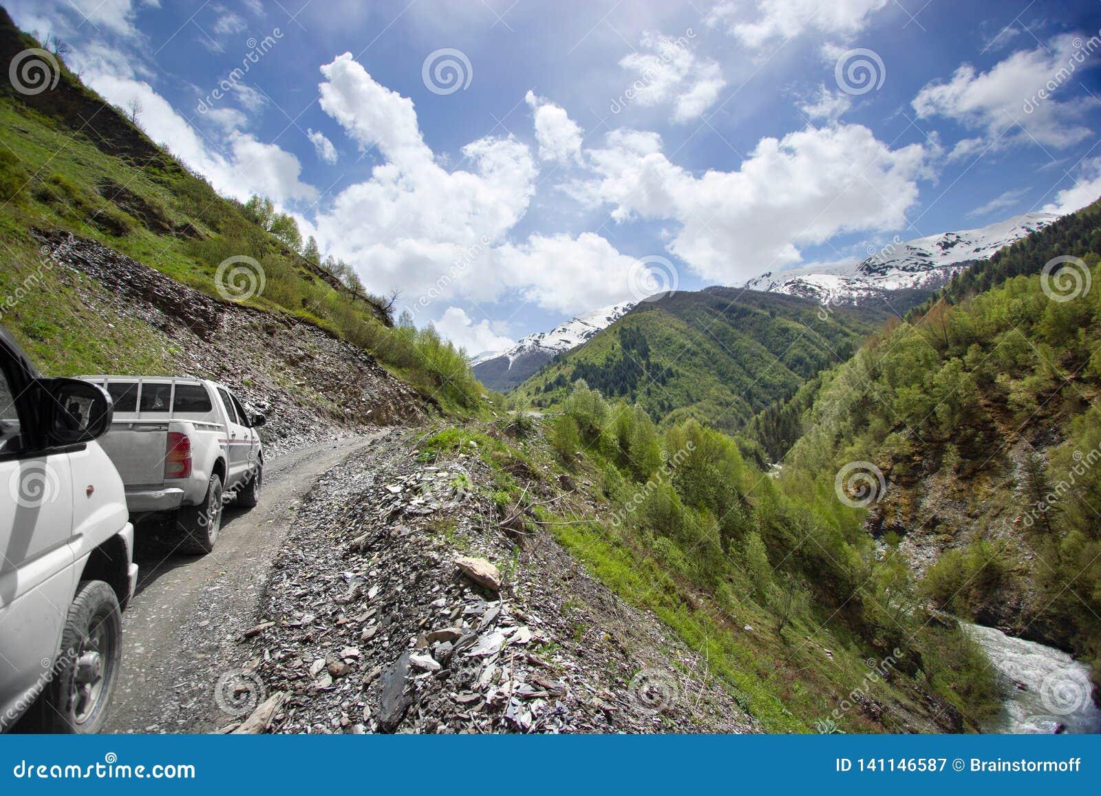 Twee auto s op een kronkelige weg in de bergen, bergpieken op de sneeuw en de groene heuvelsachtergrond