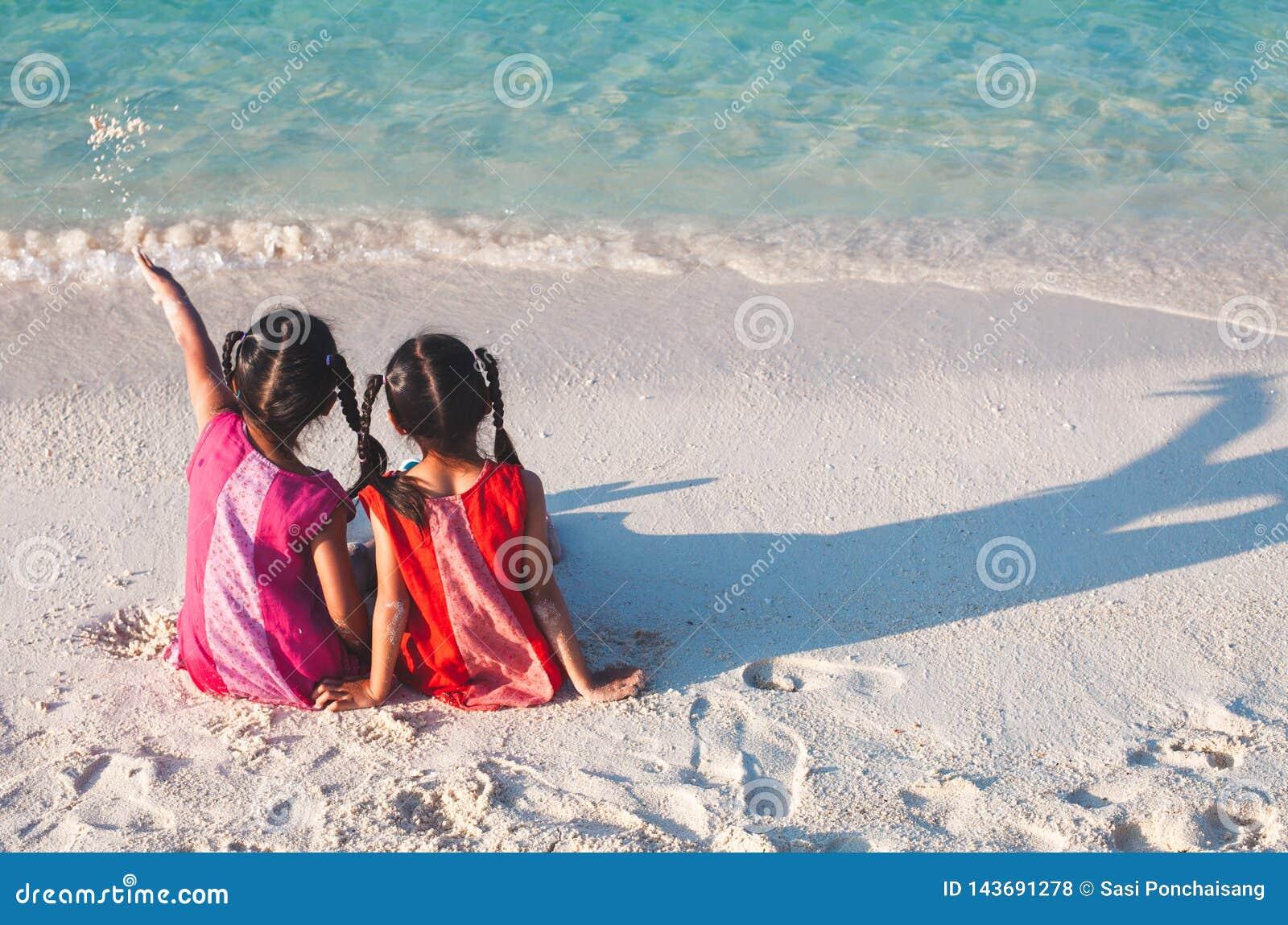 Twee Aziatische kleine kindmeisjes die en samen op het strand dichtbij het mooie overzees in de zomervakantie zitten spelen