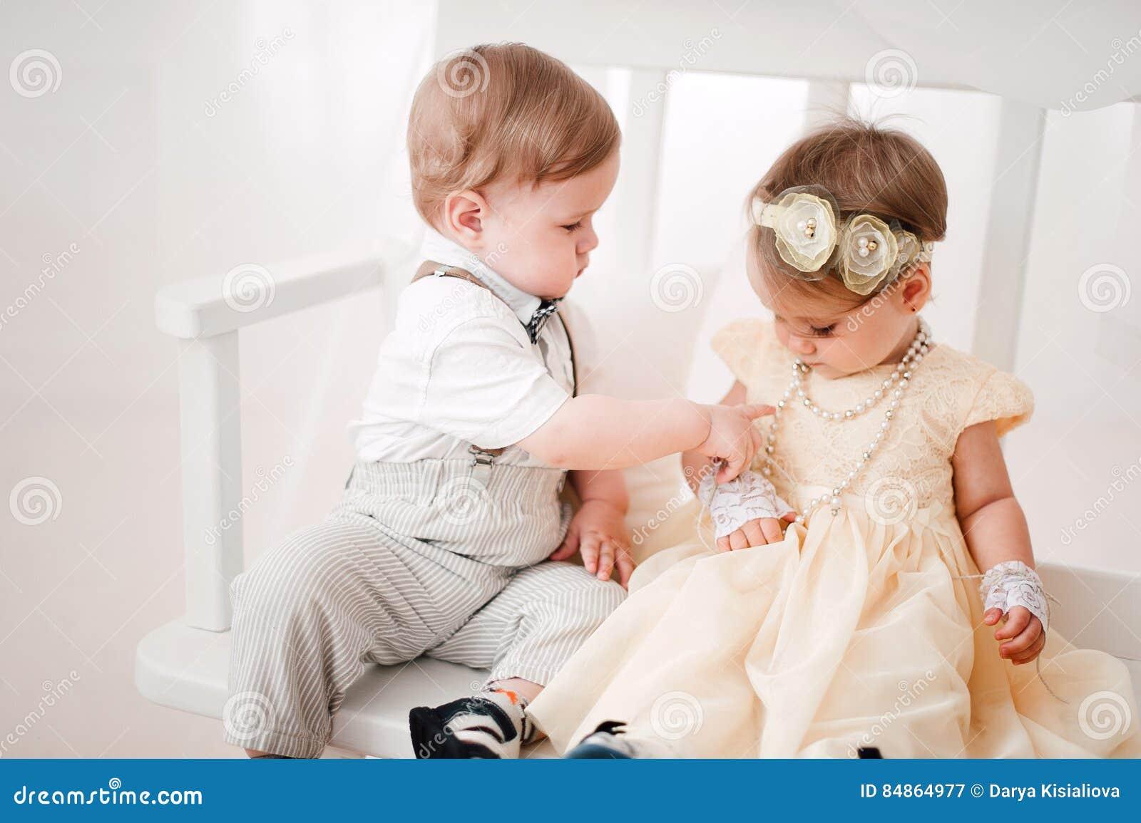 Twee babyshuwelijk de jongen en het meisje kleedden zich als bruid en bruidegom stock foto - Twee meisjes en een jongen ...