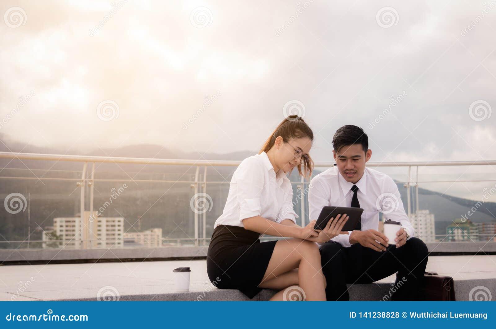 Twee bedrijfsmensen die op dakvloer zitten en digitale tablet samen gebruiken op buiten bedrijfskantoor