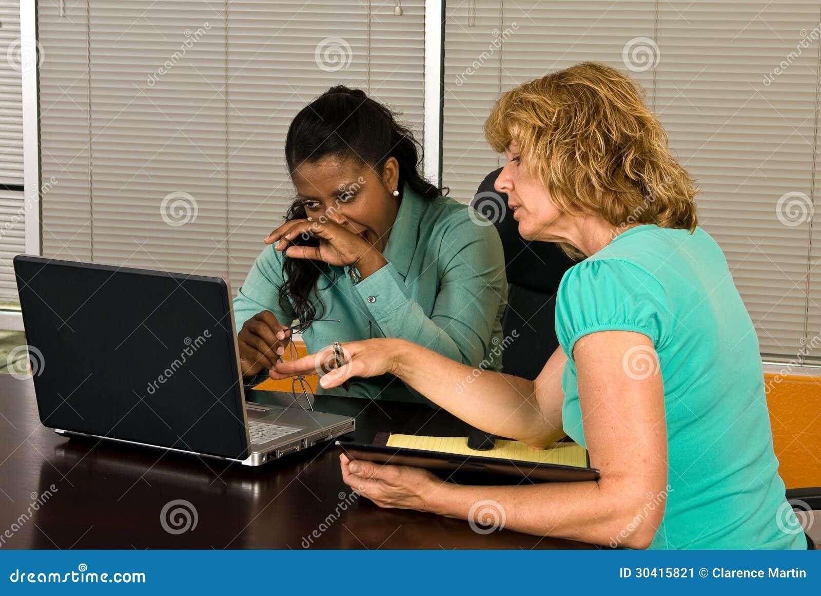 Twee bedrijfsvrouwen bekijken een laptop computer