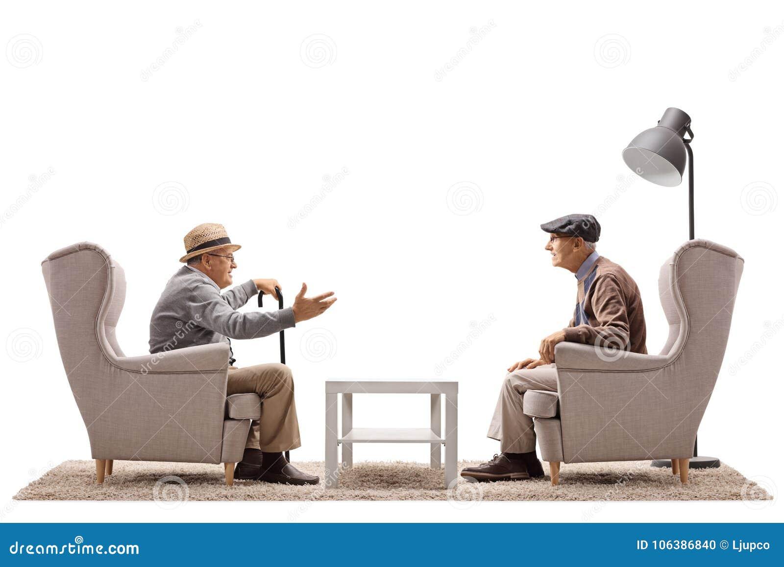Twee bejaarden gezet in leunstoelen die een gesprek hebben