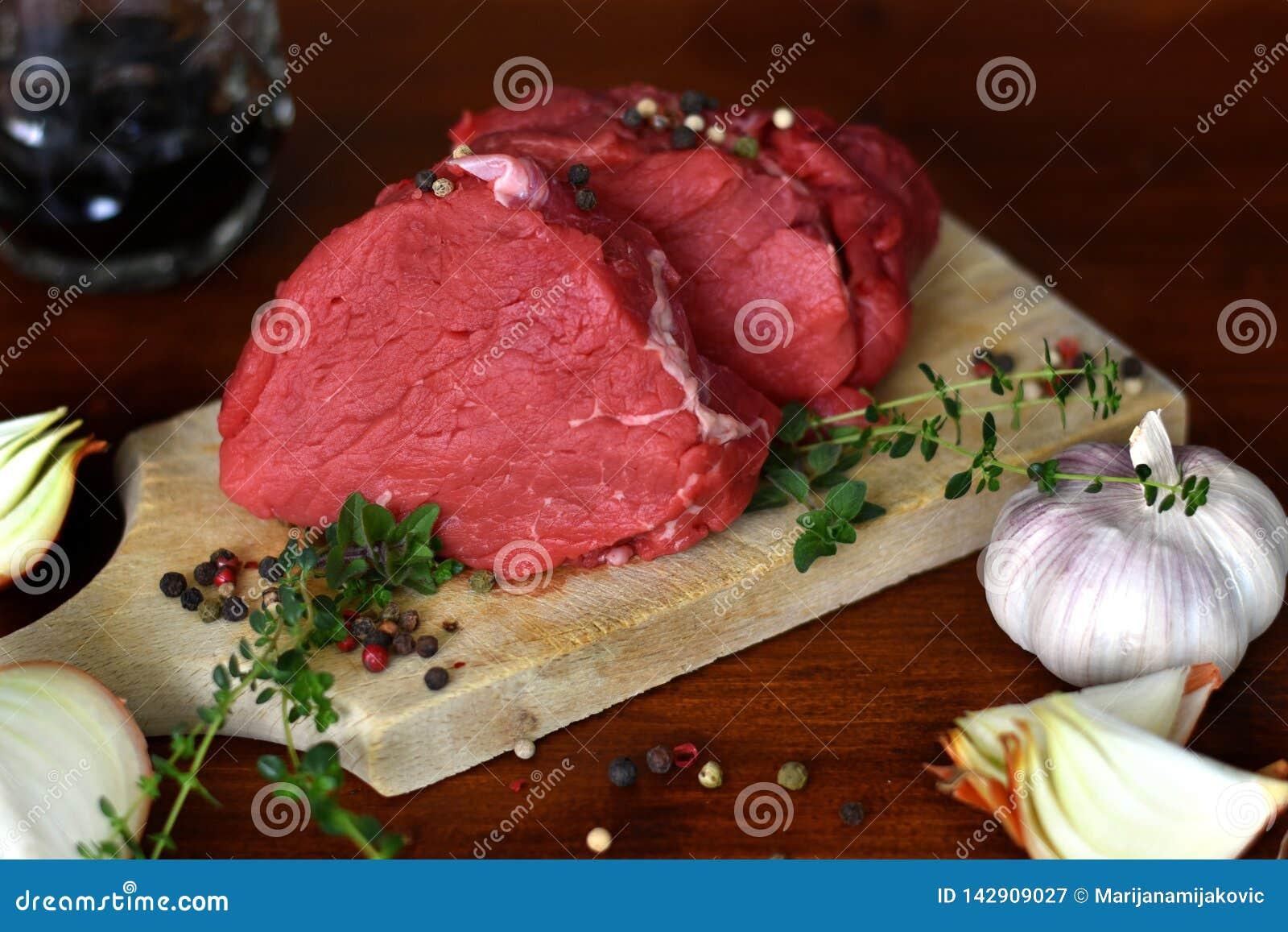 Twee besnoeiingen van vers ruw rundvleeslapje vlees op de houten scherpe raad