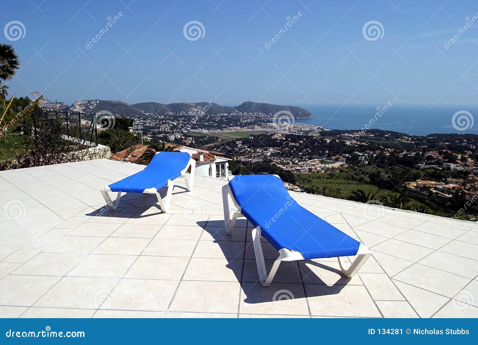 Twee blauwe sunbeds op terras in de zon met verbazende meningen van de oceaan