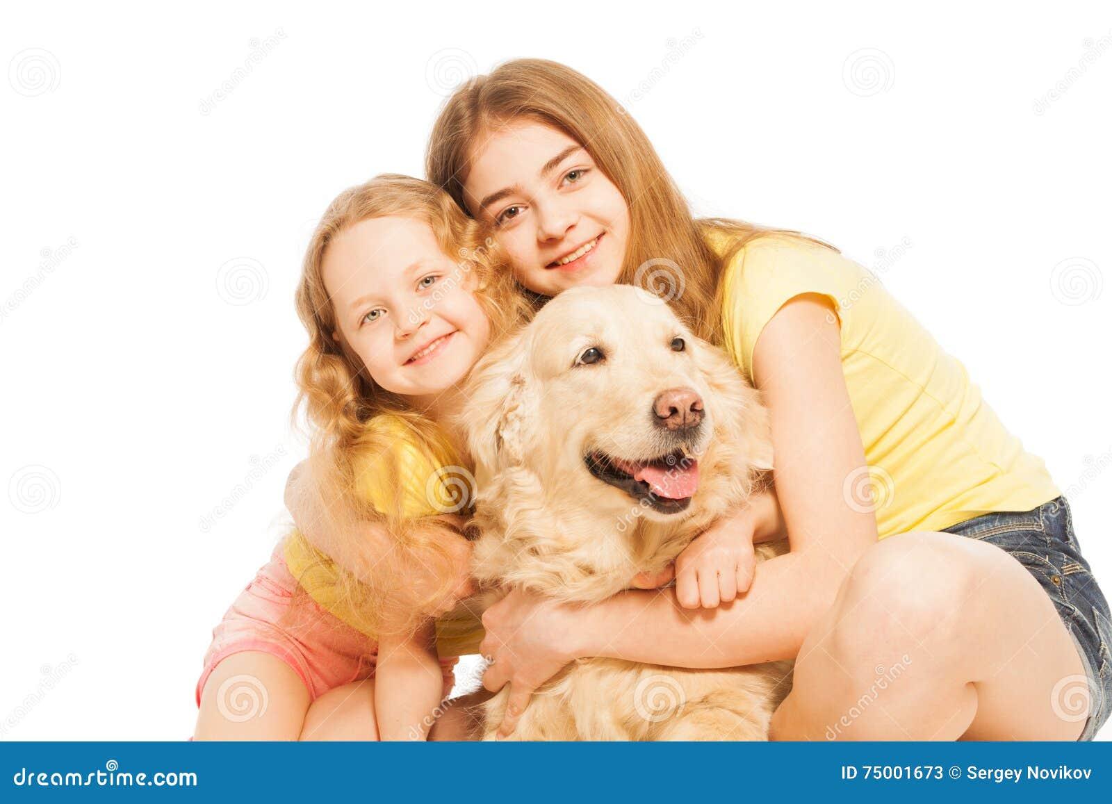 Twee blonde meisjes die hun Golden retriever koesteren