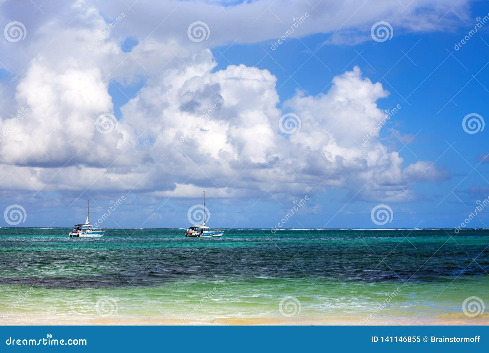 Twee boten op azuurblauwe overzees, Caraïbisch strand, blauwe hemel en grote witte wolkenachtergrond