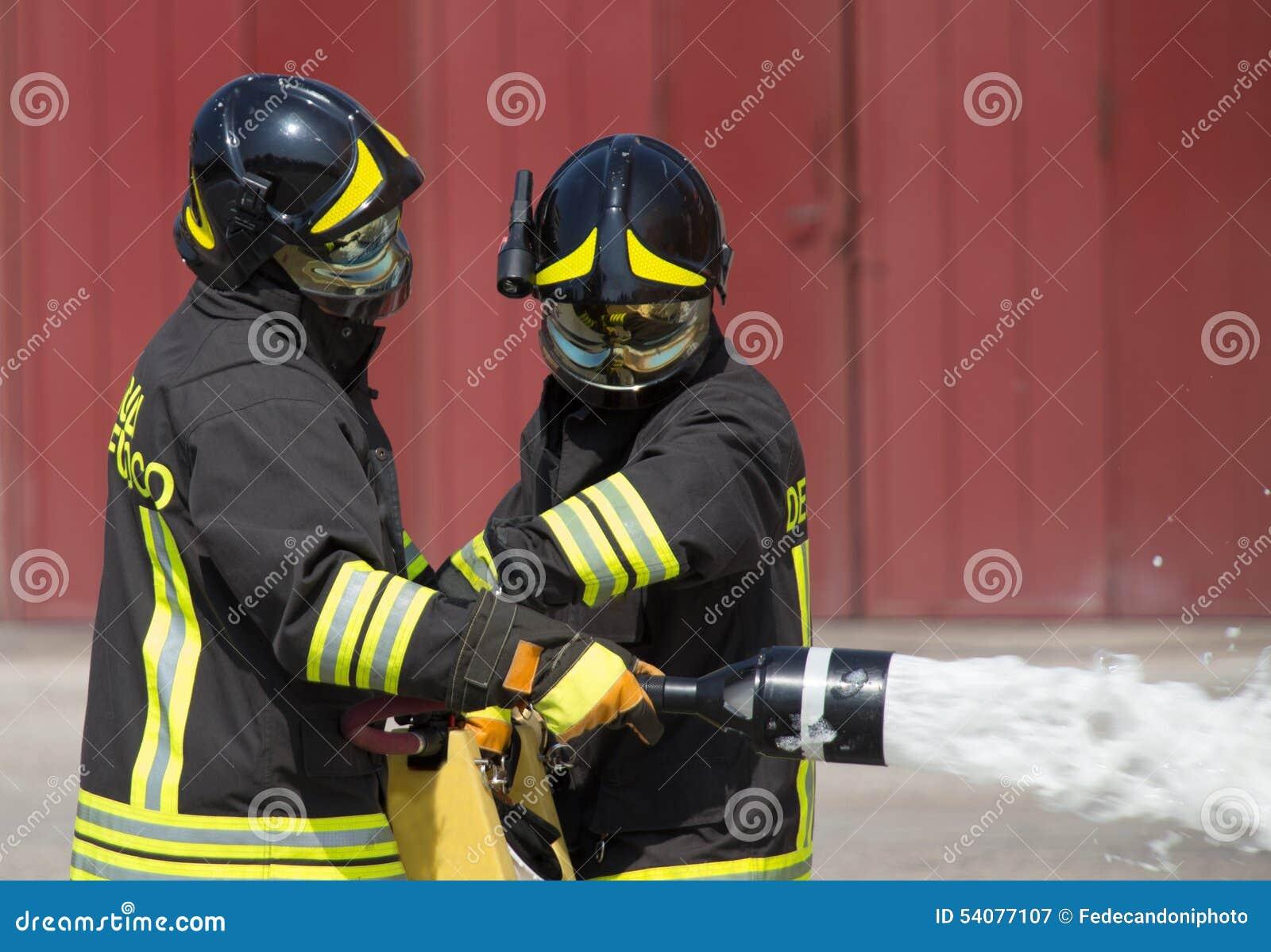 Twee brandweerlieden in actie met schuim