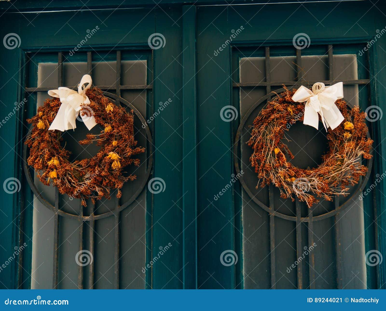 Twee bruine kronen met bogen op groene deuren