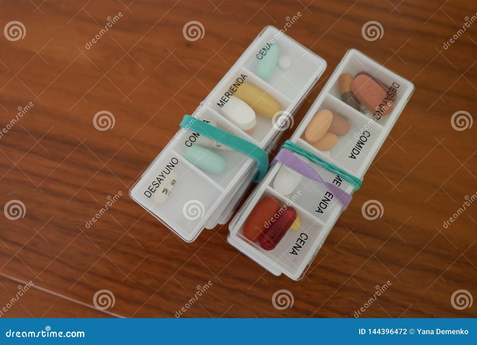 Twee bundels van dozen met dagelijkse dosissen tabletten van verschillende kleuren