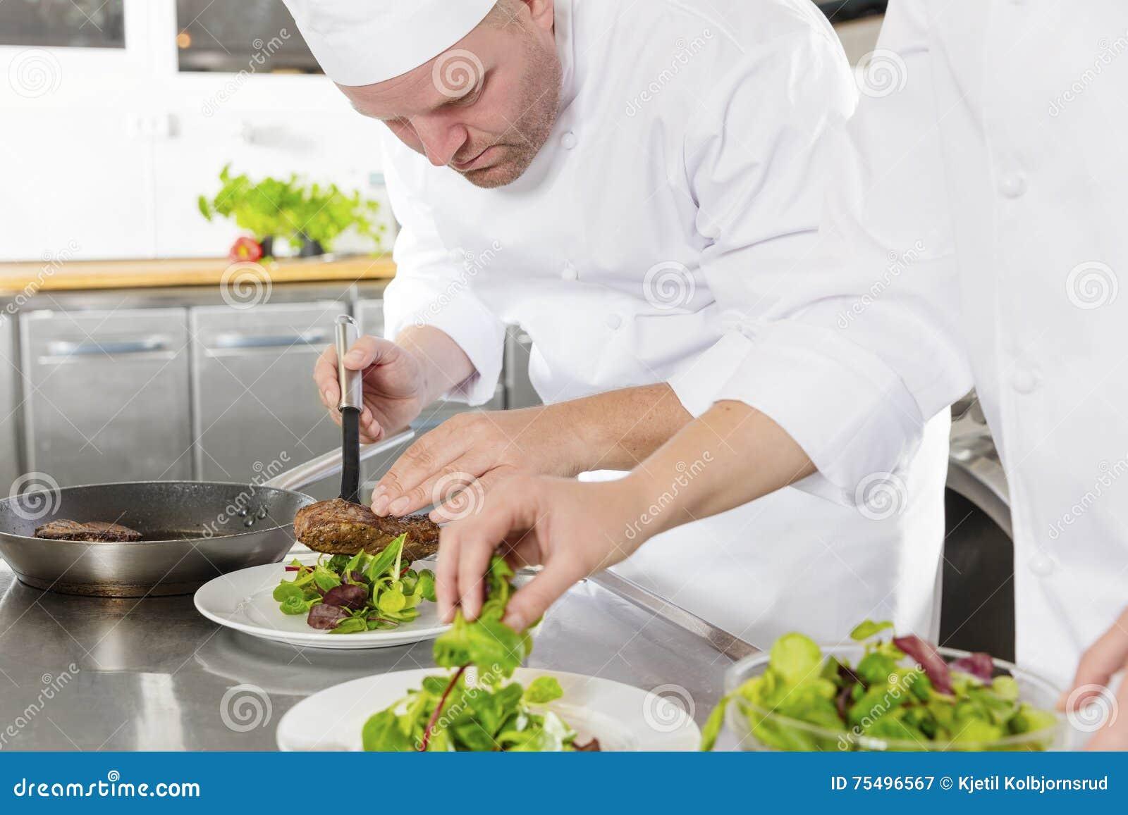 Twee chef-koks bereidt lapje vleesschotel bij gastronomisch restaurant voor