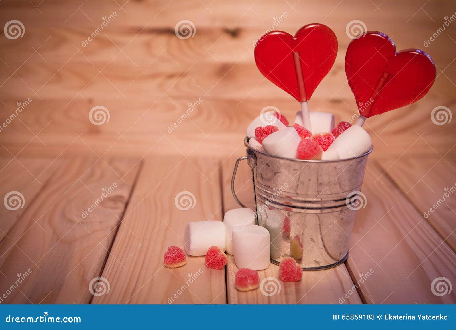Twee die Lollyshart in Kleine emmer met snoepjes op houten wordt gevormd
