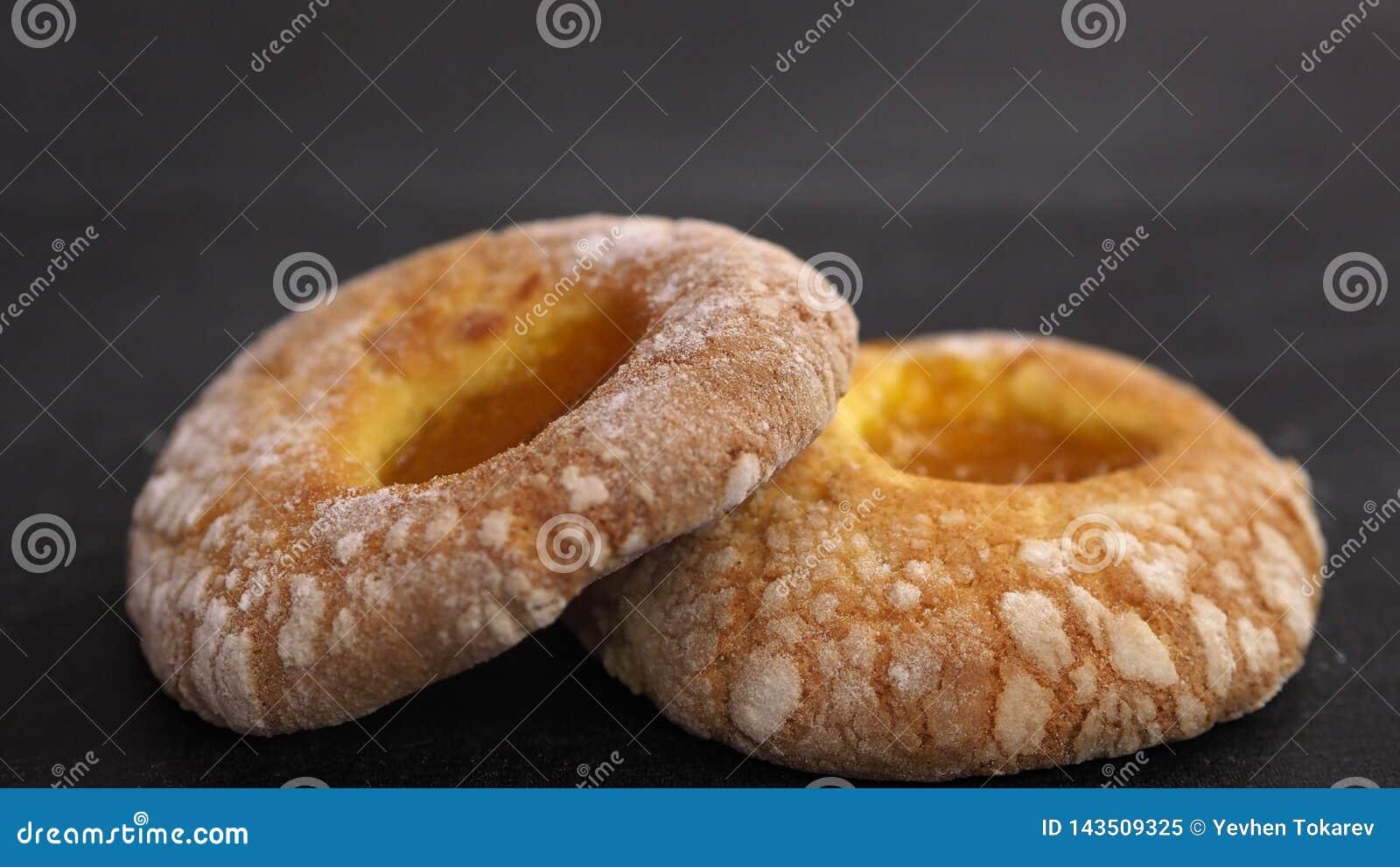 Twee donuts met abrikoos blokkeren op centrum een zwarte achtergrond