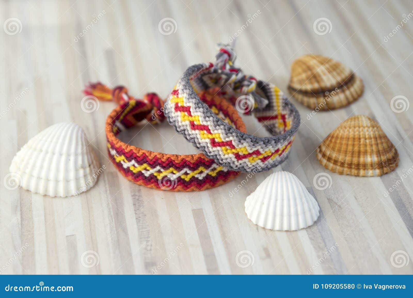 Twee eenvoudige met de hand gemaakte eigengemaakte natuurlijke geweven armbanden van vriendschap op witte houten lijst en overzee