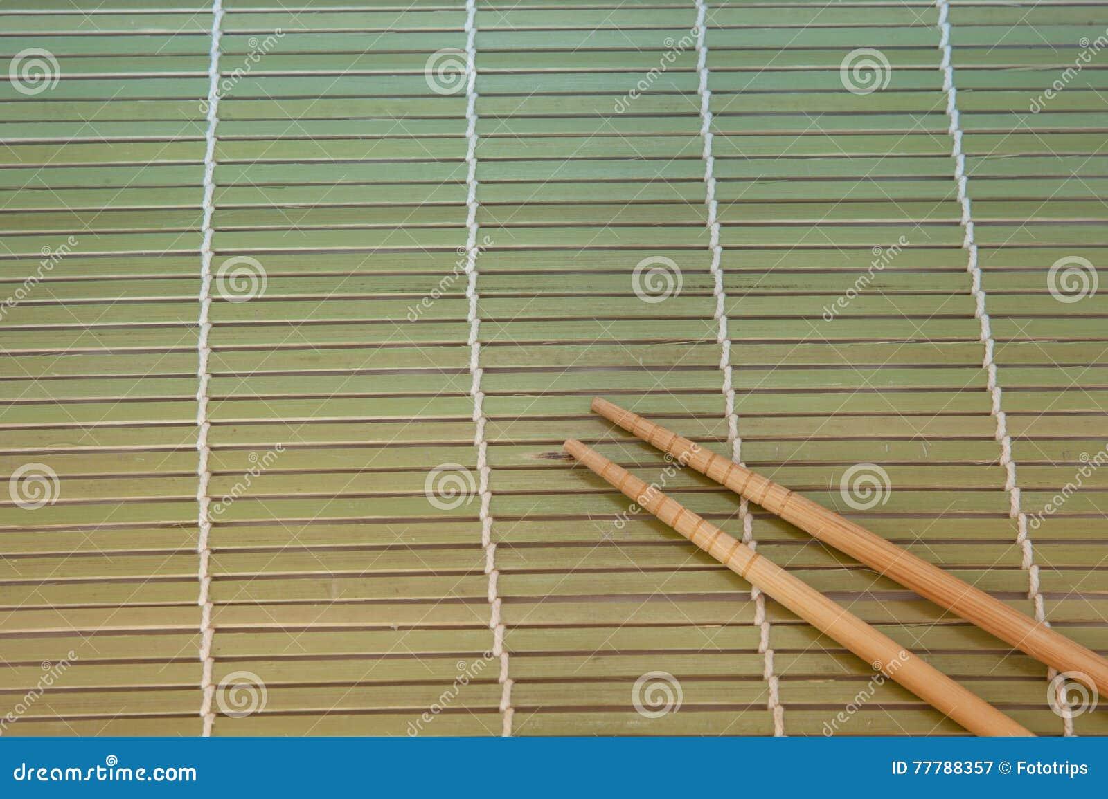 Twee eetstokjes op een achtergrond van de bamboemat
