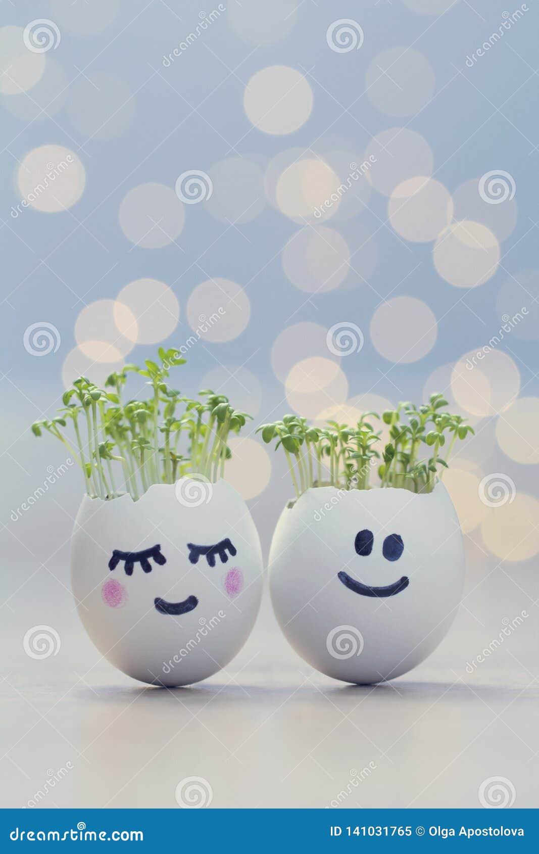 Twee eierschalenlachebekjes met tuinkersspruiten Pasen-eierschaalplanters