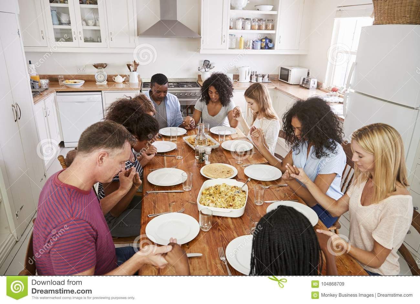 Twee Families die Grace Before Eating Meal Together zeggen