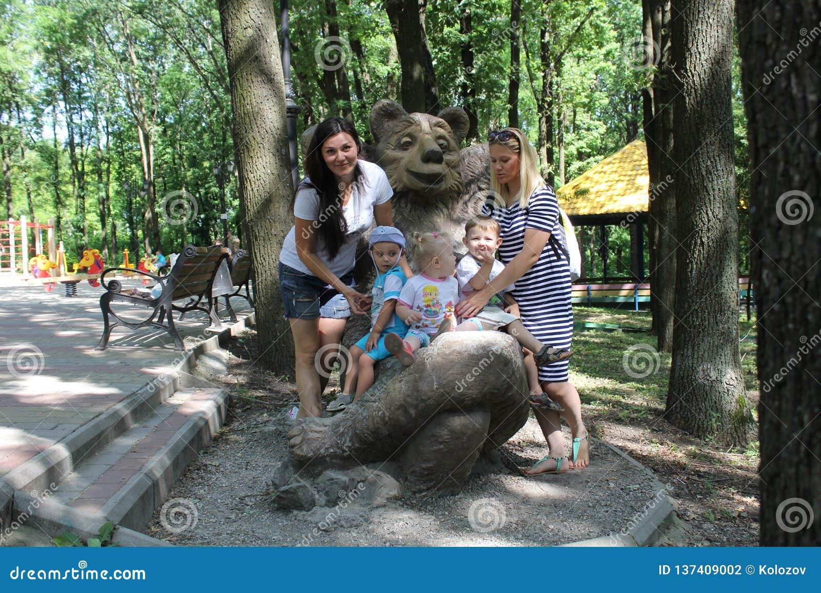 Twee families met drie kinderen Moeders en siblings jonge geitjes die pret in openlucht in tuin hebben