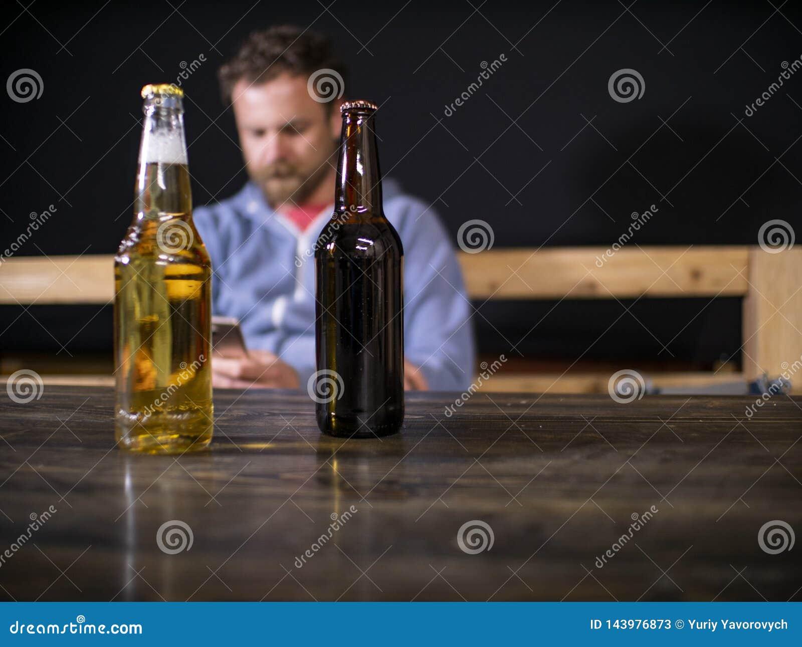 Twee flessen bier bevinden zich op de lijst tegen de achtergrond van een zittingsmens die de telefoon onderzoekt