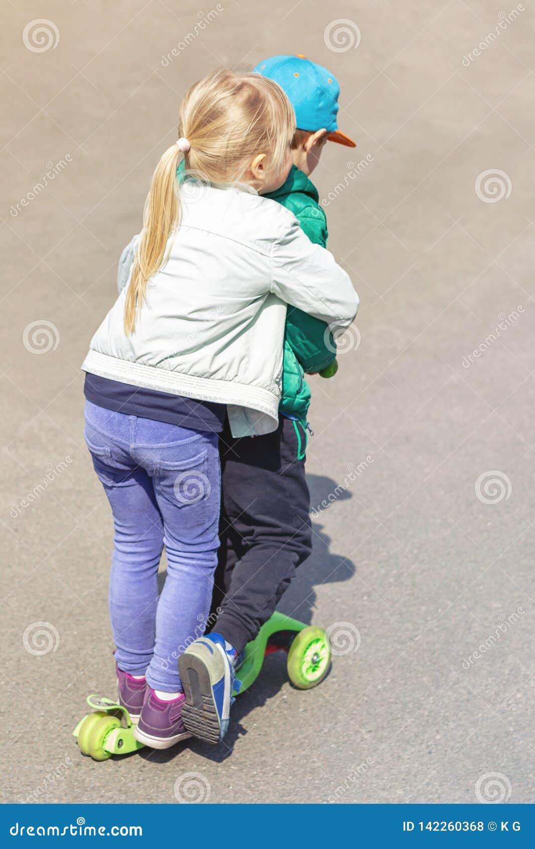 Twee frinedsjongen en meisje die pret hebben die één autoped samen gelijktijdig berijden Kinderensiblings, broer en zuster