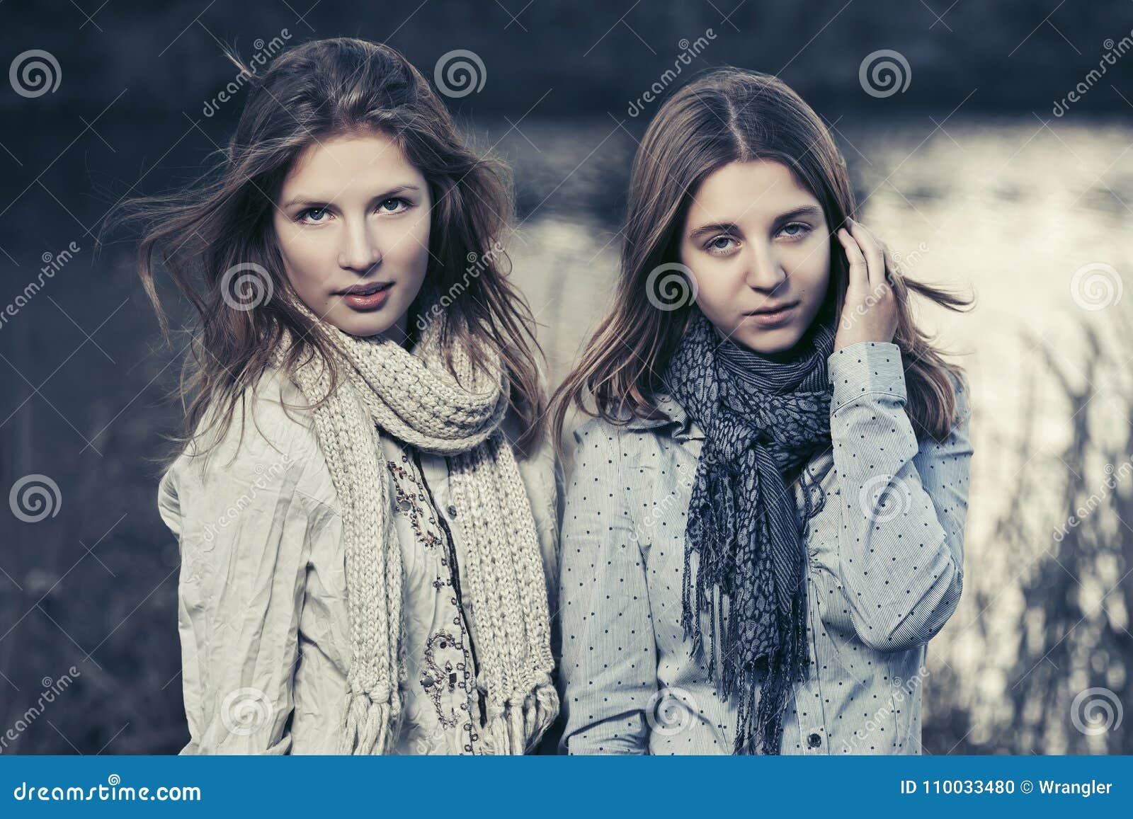 Twee gelukkige jonge maniermeisjes die door het meer lopen