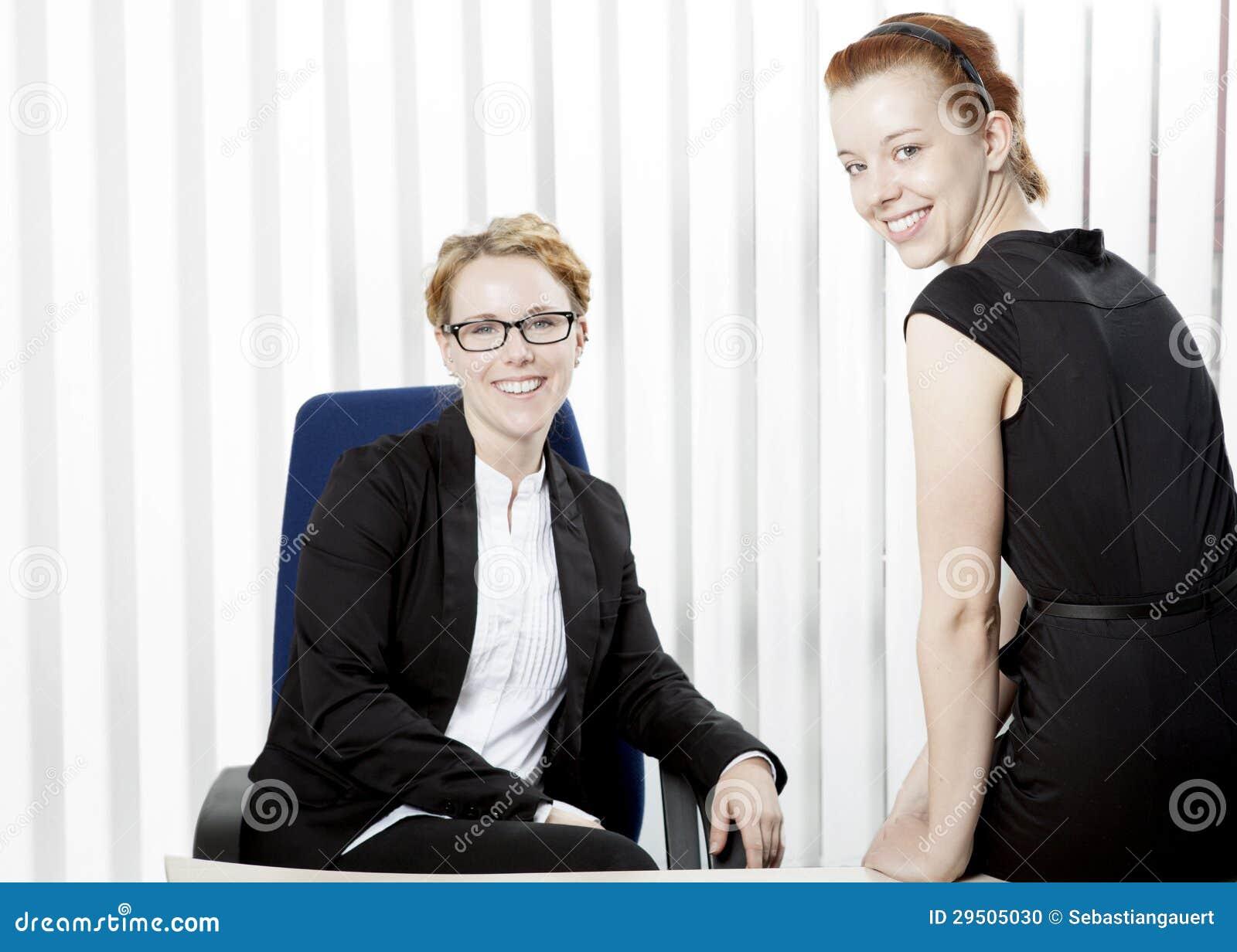 Twee gelukkige jonge vrouwen in een bureau