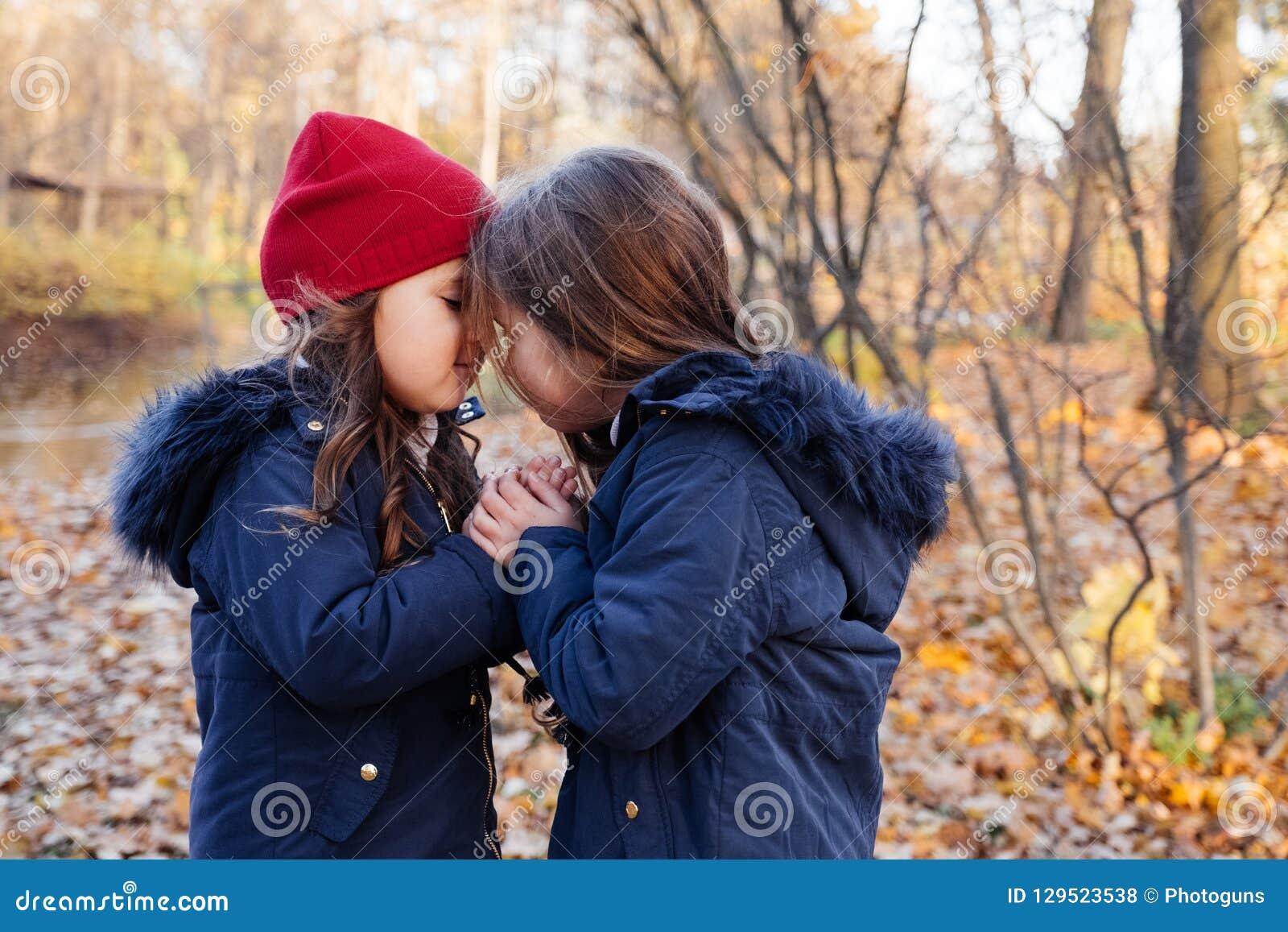 Twee gelukkige kinderen die in de herfstpark koesteren Sluit omhoog het zonnige portret van de levensstijlmanier van twee mooie K