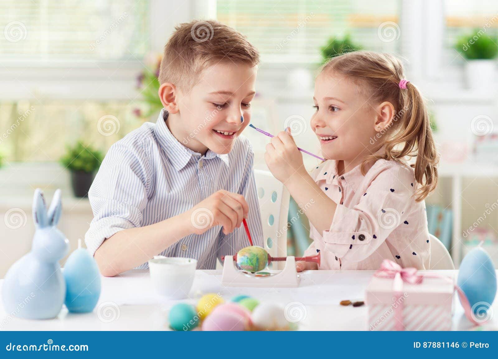 Twee gelukkige kinderen die pret hebben tijdens het schilderen eieren voor Pasen binnen
