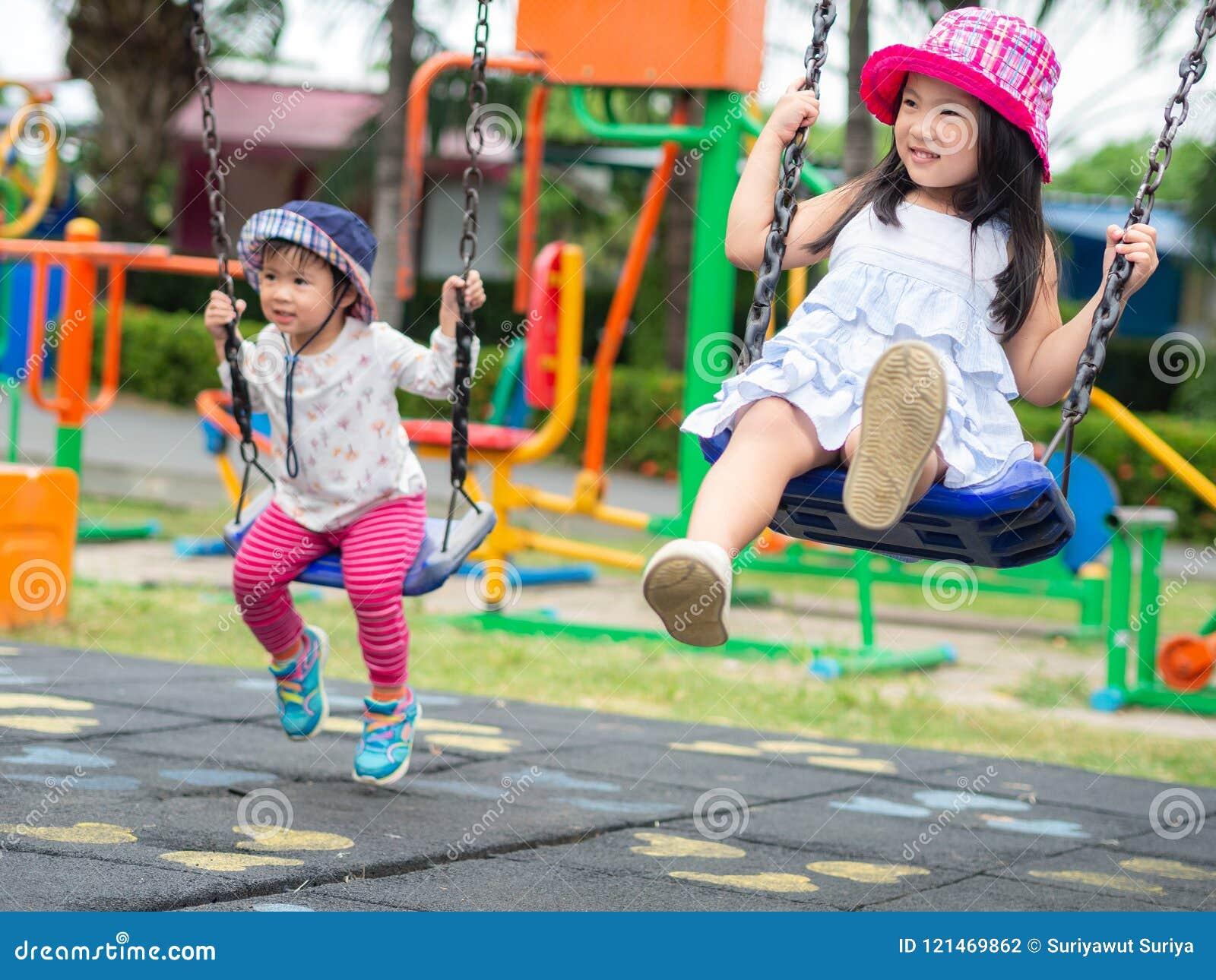 Twee Gelukkige meisjes die schommeling spelen bij de speelplaats Gelukkig, F
